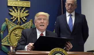 President Donald Trump, left, with Defense Secretary James Mattis, right, watching, explains the executive action on extreme vetting that he is about to sign at the Pentagon in Washington, Friday, Jan. 27, 2017. (AP Photo/Susan Walsh)
