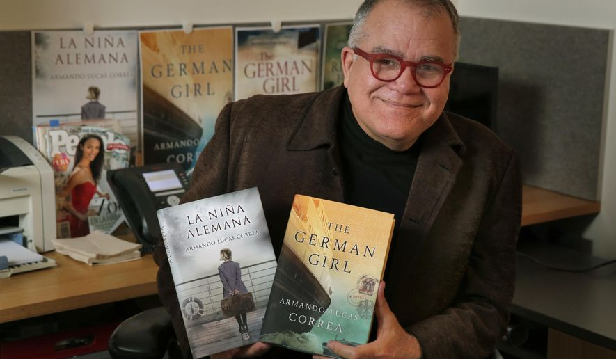 """Armando Correa, Editor in Chief of People en Espanol, poses with the Spanish and English versions of his novel, """"The German Girl,"""" in his office in New York, Tuesday, Jan. 24, 2017. (AP Photo/Richard Drew)"""