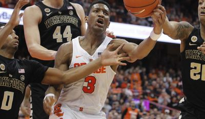 Syracuse's Andrew White, center, grabs a rebound away from Wake Forest's Brandon Childress, left, and Wake Forest's John Collins, right, in the second half of an NCAA college basketball game in Syracuse, N.Y., Tuesday, Jan. 24, 2017. Syracuse won 81-76. (AP Photo/Nick Lisi)