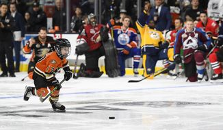 Ryker Kesler, left, son of Anaheim Ducks' Ryan Kesler, right, gets ready to shoot on Montreal Canadiens goalie Carey Price as members of the All-Star team cheer him on during the Shootout portion of the NHL All-Star Skills Competition, Saturday, Jan. 28, 2017, in Los Angeles. (AP Photo/Mark J. Terrill)