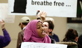 """Nicole, who didn't want to give her last name, protests against President Donald Trump's executive order barring Muslims from certain middle eastern countries from entering the United States at DFW airport, Saturday, Jan. 28, 2017. Meanwhile Democrats gathered in Houston for a """"Future Forum"""" vowed to resist President Trump's immigration policies.  (Brandon Wade/Star-Telegram via AP)"""