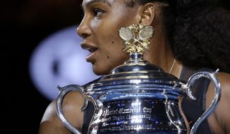 United States' Serena Williams holds her trophy after defeating her sister Venus during their women's singles final at the Australian Open tennis championships in Melbourne, Australia, Saturday, Jan. 28, 2017. (AP Photo/Aaron Favila)