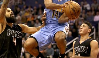 Denver Nuggets guard Gary Harris (14) drives between Phoenix Suns center Tyson Chandler (4) and Devin Booker in the first quarter during an NBA basketball game, Saturday, Jan. 28, 2017, in Phoenix. (AP Photo/Rick Scuteri)