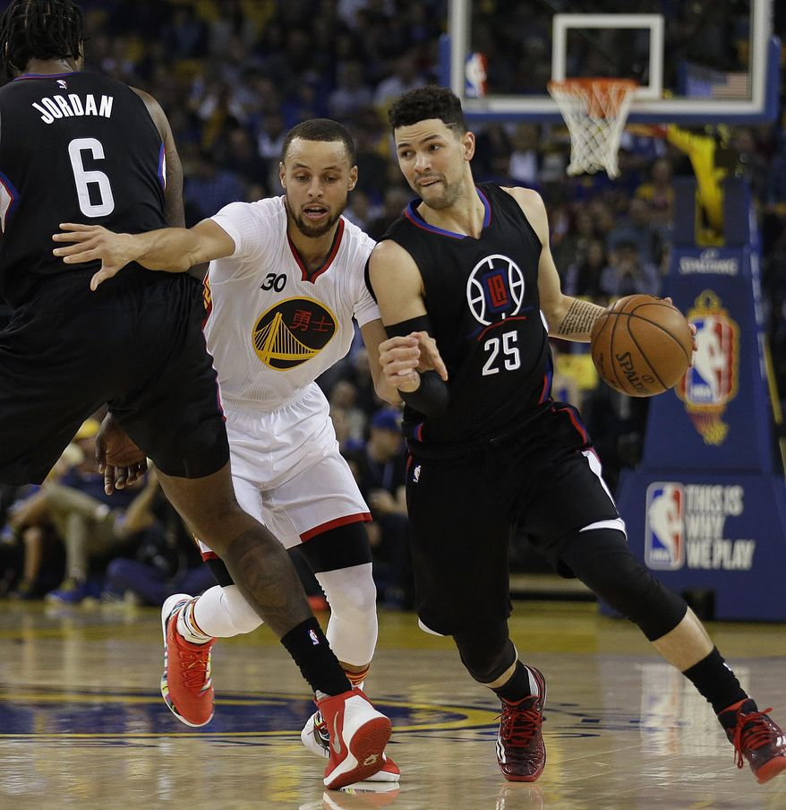 Los Angeles Clippers' Austin Rivers, right, drives the ball as teammate DeAndre Jordan (6) blocks Golden State Warriors' Stephen Curry (30) during the first half of an NBA basketball game Saturday, Jan. 28, 2017, in Oakland, Calif. (AP Photo/Ben Margot)