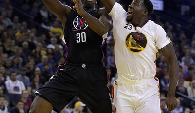Los Angeles Clippers' Brandon Bass, left, shoots against Golden State Warriors' Draymond Green (23) during the first half of an NBA basketball game Saturday, Jan. 28, 2017, in Oakland, Calif. (AP Photo/Ben Margot)