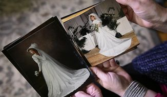 In this Monday, Jan. 23, 2017 photo, Shannon McNamara, left, and Kim Jones show the similarities of their wedding dresses as they put their wedding pictures side by side in Franklin, Tenn. The two women got sent home with each other's wedding dresses 30 years ago and only recently discovered the mixup. (Lacy Atkins/The Tennessean via AP)