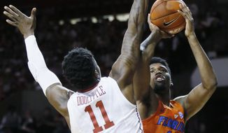Florida center Kevarrius Hayes (13) shoots in front of Oklahoma forward Kristian Doolittle (11) in the first half of an NCAA college basketball game in Norman, Okla., Saturday, Jan. 28, 2017. (AP Photo/Sue Ogrocki)