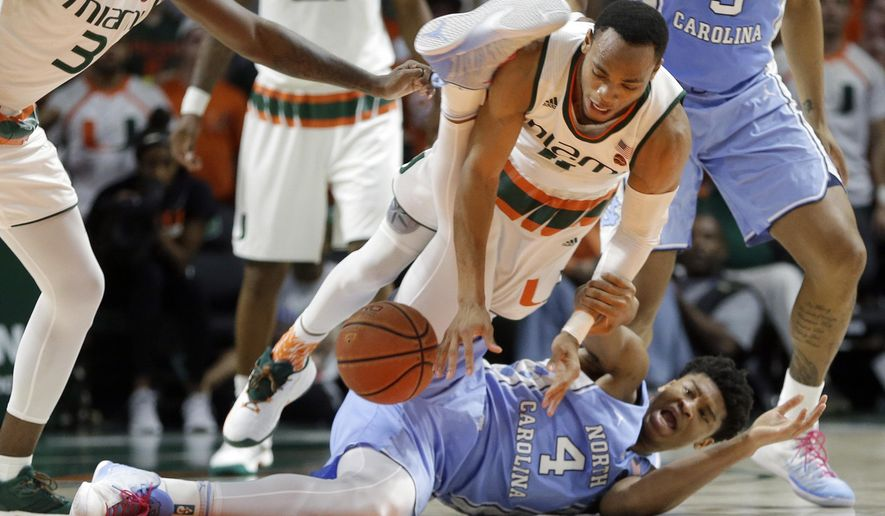 Miami guard Bruce Brown (11) struggles with North Carolina forward Isaiah Hicks (4) for the ball in the first half of an NCAA college basketball game, Saturday, Jan. 28, 2017, in Coral Gables, Fla. (AP Photo/Alan Diaz)