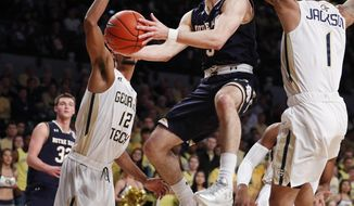 Notre Dame guard Matt Farrell (5) drives between Georgia Tech's Quinton Stephens (12) and Tadric Jackson (1) in the first half of an NCAA college basketball game Saturday, Jan. 28, 2017, in Atlanta. (AP Photo/John Bazemore)