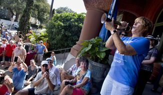 In this photo provided by the Florida Keys News Bureau, marathon swimmer Diana Nyad, right, blows a bugle at the dedication of a new exhibit showcasing her 2013 Cuba-to-Key West swim at the Key West Art & Historical Society's Custom House Museum Friday, Jan. 27, 2017, in Key West, Fla. Nyad donated her swimsuit, goggles and a jellyfish mask she used to complete an almost 111-mile swim, becoming the first person to cross the Florida Straits without a shark cage. (Carol Tedesco/Florida Keys News Bureau via AP)