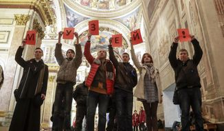 Protesters against the transfer of St. Isaac's Cathedral to the Russian Orthodox Church hold letters reading 'The museum!' standing inside the St. Isaac's Cathedral in St.Petersburg, Russia, Saturday, Jan. 28, 2017. Over 2,000 people rallied in St. Petersburg on Saturday to protest plans by the city authorities to give a landmark cathedral to the Russian Orthodox Church amid an increasingly passionate debate over the relationship between the church and state. (AP Photo/Dmitri Lovetsky)