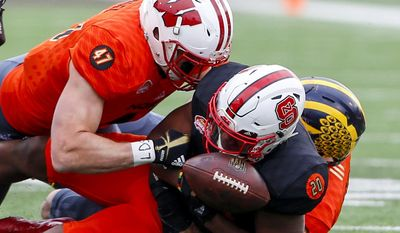 South squad running back Matt Dayes of North Carolina State (20) fumbles the ball as he is tackled by North squad outside linebacker Vince Biegel of Wisconsin (47) and North squad inside linebacker Ben Gedeon of Michigan (42) during the first half of the Senior Bowl NCAA college football game, Saturday, Jan. 28, 2017, at Ladd-Peebles Stadium in Mobile, Ala. (AP Photo/Butch Dill)
