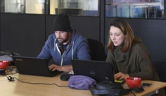 This photo taken Jan. 16, 2017, shows Tim and Ewa North working remotely from their computers at Columbia Collective on Main Street in downtown Vancouver, Wash. There are more than 50 members at Columbia Collective, now in a 1,500-square-foot space at 810 Main St. Members pay a monthly rate to access a place they say is more conducive for work than the library or their homes.  (Ariane Kunze/The Columbian via AP)