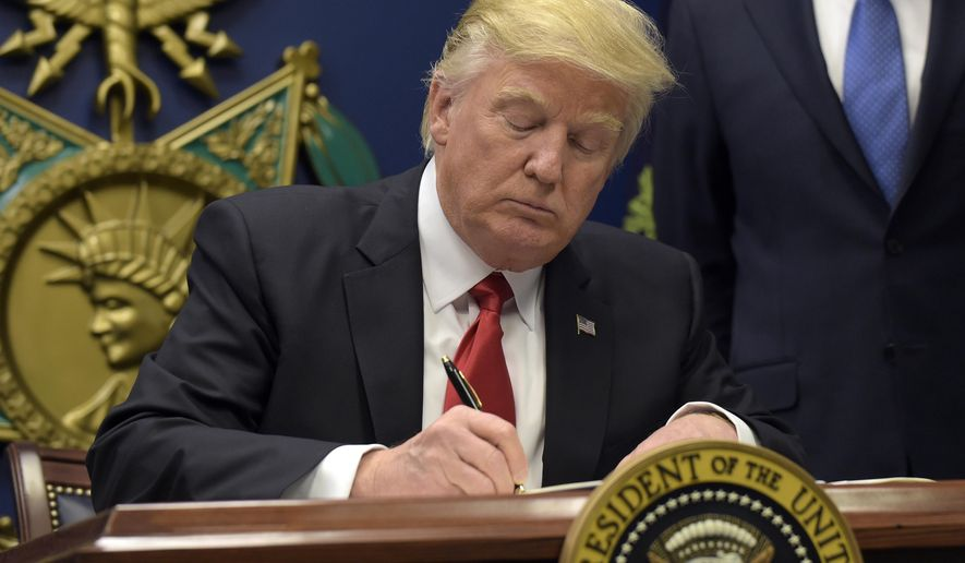 President Donald Trump signs an executive order on extreme vetting during an event at the Pentagon in Washington, Friday, Jan. 27, 2017. (AP Photo/Susan Walsh)