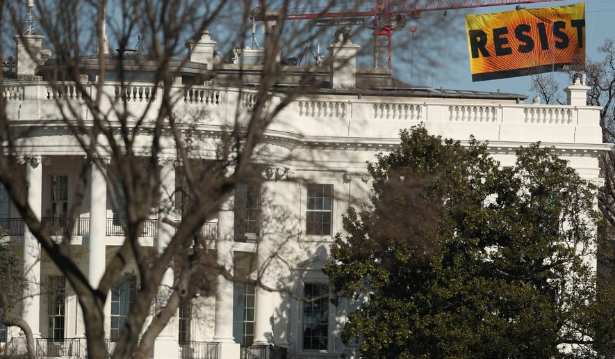 Greenpeace demonstrators used a crane to hang a banner near the White House last week. It was one part of a multipronged strategy to combat the Trump administration's purported war against the science of climate change. (Associated Press)