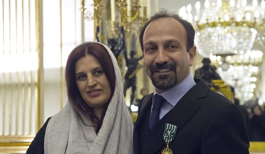 In this Feb. 27, 2014 file photo, Iranian film director Asghar Farhadi, right, and his wife Parisa, pose after he was awarded the Officer of the Order of Arts and Letters medal, at the French Ministry of Culture, in Paris, France. The Oscar-nominated Iranian director says he will not attend this years Academy Awards because of a travel ban imposed by President Donald Trump. Farhadi, whose film, The Salesman, was nominated for best foreign film, says the uncertainty surrounding his ability to travel to the United States was in no way acceptable, and that he would not attend the ceremony even if an exception to the ban were possible. (AP Photo/Michel Euler, File)