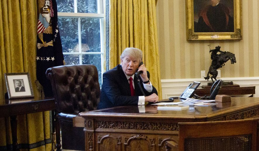 President Donald Trump speaks on the phone with King of Saudi Arabia Salman bin Abd al-Aziz Al Saud in the Oval Office at the White House in Washington, Sunday, Jan. 29, 2017. (AP Photo/Manuel Balce Ceneta)