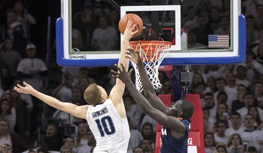 Villanova's Donte DiVincenzo. center, puts back the shot by Josh Hart, bottom, for the game winning score with Virginia's Marial Shayok, right and Ty Jerome , left, defending during the second half of an NCAA basketball game, Sunday, Jan. 29, 2017, in Philadelphia. Villanova won 61-59. (AP Photo/Chris Szagola)