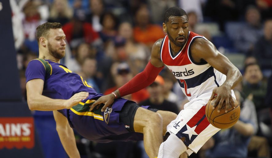 Washington Wizards guard John Wall (2) recovers the ball after knocking into New Orleans Pelicans forward Donatas Motiejunas in the second half of an NBA basketball game in New Orleans, Sunday, Jan. 29, 2017. The Wizards won 107-94. (AP Photo/Max Becherer)