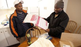 """ADVANCE FOR WEEKEND EDITIONS, JAN. 28-29 - In this Wednesday, Jan. 18, 2017 photo, Asukulu Ramadhani and Davis Balondani, prepare to hang a calendar as they helped setup an apartment in Lexington, Ky. St. Luke United Methodist Church, has """"adopted"""" a Congolese refugee family through Kentucky Refugee Ministries. The team, who all came here through KRM themselves, moved donated furniture into the family's apartment to make it ready for their arrival tonight. St. Luke United Methodist Church hosts a Swahili-speaking service that draws about 115 Congolese each week, and many of them are refugees. (Charles Bertram/Lexington Herald-Leader via AP)"""