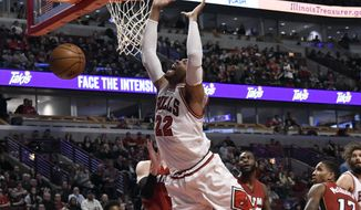 Chicago Bulls forward Taj Gibson (22) is fouled while going to the basket against the Miami Heat during the second half of an NBA basketball game in Chicago, Friday, Jan. 27, 2017. The Heat won 100-88. (AP Photo/David Banks)