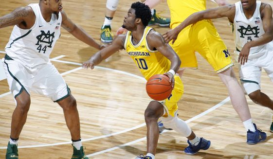 Michigan's Derrick Walton, center, drives between Michigan State's Nick Ward, left, and Cassius Winston, right, during the first half of an NCAA college basketball game, Sunday, Jan. 29, 2017, in East Lansing, Mich. (AP Photo/Al Goldis)