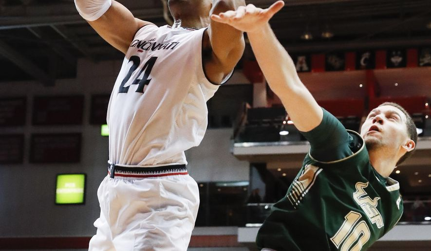Cincinnati's Kyle Washington (24) shoots against South Florida's Michael Bibby (10) in the first half of an NCAA college basketball game, Sunday, Jan. 29, 2017, in Cincinnati. (AP Photo/John Minchillo)