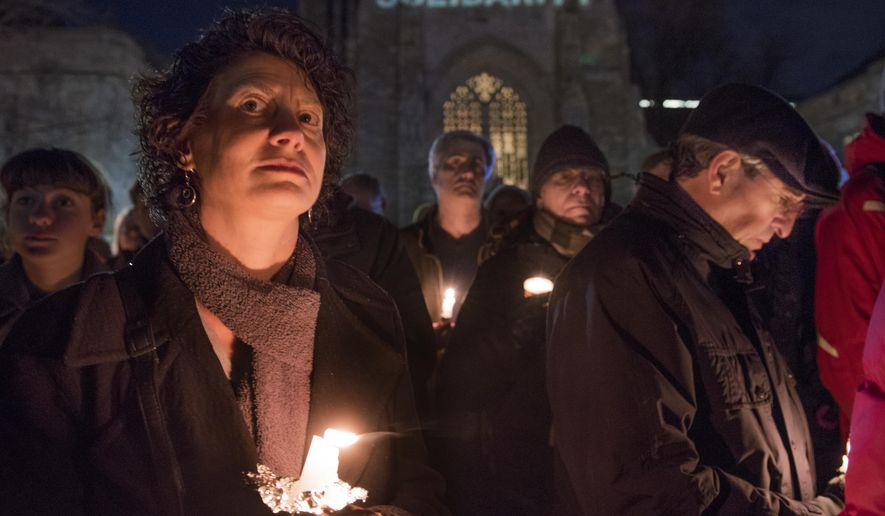"""Tamar Gendler, front left, Dean of Arts and Sciences at Yale, and Yale President Peter Solovey, front right, listen to speakers in front of Sterling Memorial Library at Yale University in New Haven, Conn., Sunday, Jan. 29, 2017. Hundreds turned out for the vigil in support of refugees. Organizers projected the word """"solidarity"""" on the library. (Melanie Stengel/Hartford Courant via AP)"""