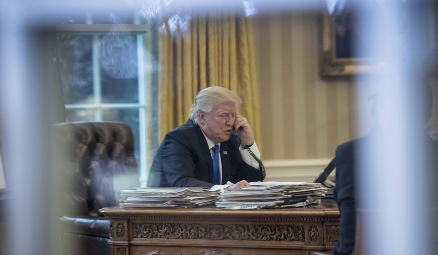President Donald Trump speaks on the phone with German Chancellor Angela Merkel, Saturday, Jan. 28, 2017, in the Oval Office at the White House in Washington. (AP Photo/Andrew Harnik)