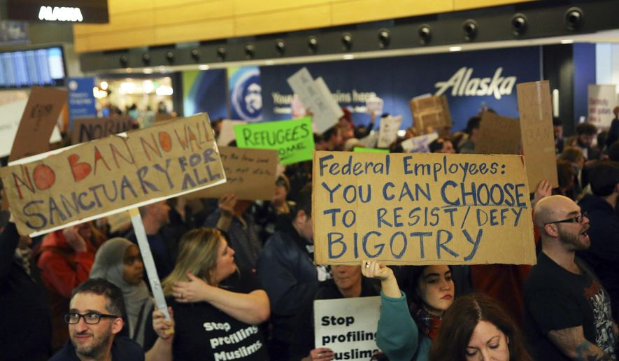 More than 1,000 people gather at Seattle-Tacoma International Airport, to protest President Donald Trump's order that restricts immigration to the U.S., Saturday, Jan. 28, 2017, in Seattle. President Trump signed an executive order Friday that bans legal U.S. residents and visa-holders from seven Muslim-majority nations from entering the U.S. for 90 days and puts an indefinite hold on a program resettling Syrian refugees. (Genna Martin/seattlepi.com via AP)
