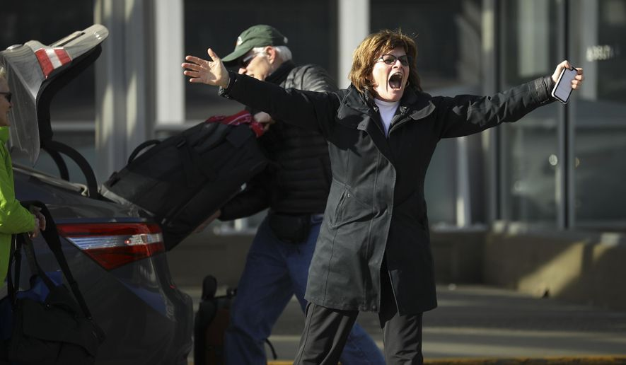 A woman dropping someone off for a flight waves back in support of the demonstrators chanting across the road at Minneapolis-St. Pail Airport in Minneapolis, Minn., Sunday, Jan. 29, 2017. Several hundred demonstrators took part in a second day of protests at the MSP airport's Terminal 1 against President Trump's new immigration policies.   (Jeff Wheeler/Star Tribune via AP)