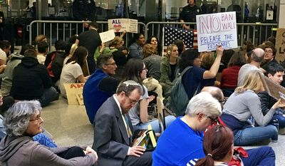 Demonstrators stage a sit-in at the international terminal while police stand and watch the protest against President Donald Trump's executive order banning travel to the U.S. by citizens of several countries at San Francisco International Airport, Sunday, Jan. 29, 2017 (AP Photo/Olga Rodriguez)
