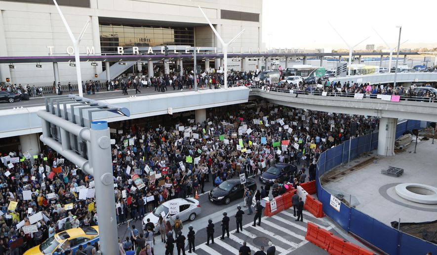 Demonstrators gather outside Tom Bradley International Terminal during a protest against President Donald Trump's travel ban on refugees and citizens of seven Muslim-majority nations, at Los Angeles International Airport on Sunday, Jan. 29, 2017. (AP Photo/Ryan Kang)