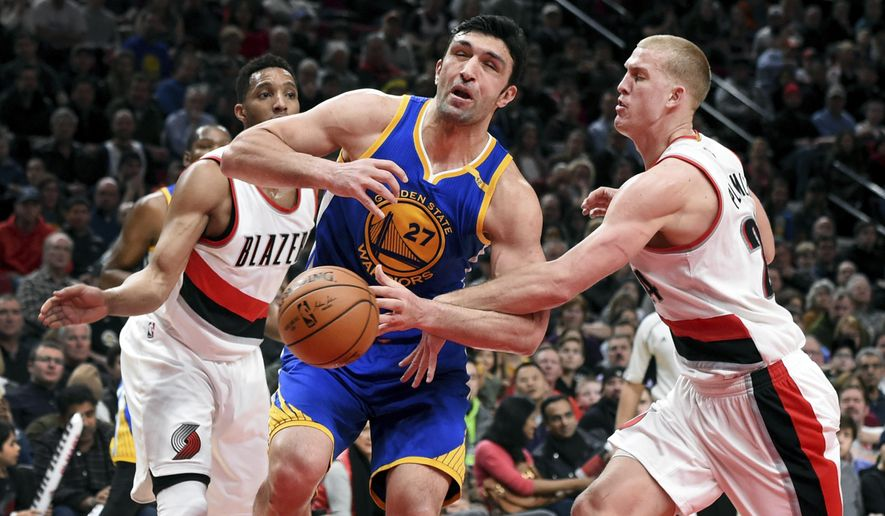 Golden State Warriors center Zaza Pachulia is fouled by Portland Trail Blazers center Mason Plumlee as he drives to the basket during the first half of an NBA basketball game in Portland, Ore., Sunday, Jan. 29, 2017. (AP Photo/Steve Dykes)