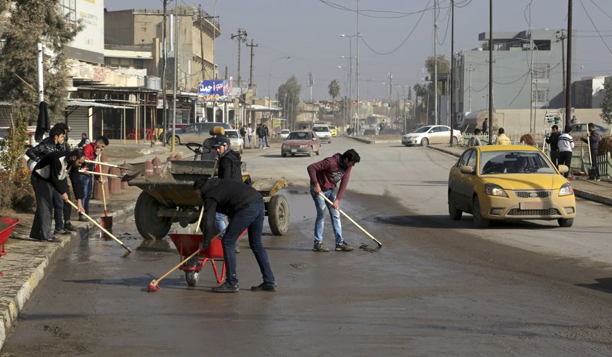 Volunteers clean their neighborhood as life begins to return to normal after the defeat of Islamic State group fighters, on the eastern side of Mosul, Iraq, Monday, Jan. 30, 2017. (AP Photo/ Khalid Mohammed)