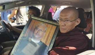 A Buddhist monk holds a portrait of Ko Ni, a legal adviser and prominent member of Myanmar's Muslim minority, as the funeral car left from his home, Monday, Jan. 30, 2017, in Yangon, Myanmar. Myanmar politicians and activists were shocked by the assassination Sunday of a longtime adviser to leader Aung San Suu Kyi are gathering at a cemetery for his funeral. (AP Photo/Esther Htusan)