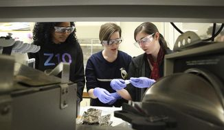Stockton University biology students, from left, Francisca Ekekwe, Valkyrie Falciani and Danielle Ertz work with spores in sterilized tubes that will be studied for agriculture in low gravity at the International Space Station, in Galloway, N.J., Monday Jan. 30 2017. Their experiments using spores were chosen by the National Center for Earth and Space Science Education (NCESSE) to go to the International Space Station (ISS) as part of Mission 11 of the Student Spaceflight Experiments Program (SSEP). (Ben Fogletto/The Press of Atlantic City via AP)