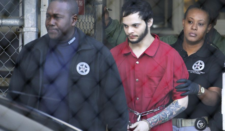 Esteban Santiago, center, is led from the Broward County jail for an arraignment in federal court, Monday, Jan. 30, 2017, in Fort Lauderdale, Fla. Santiago is charged in a 22-count federal indictment in the Jan. 6 shooting at the Fort Lauderdale-Hollywood International Airport. (AP Photo/Lynne Sladky)