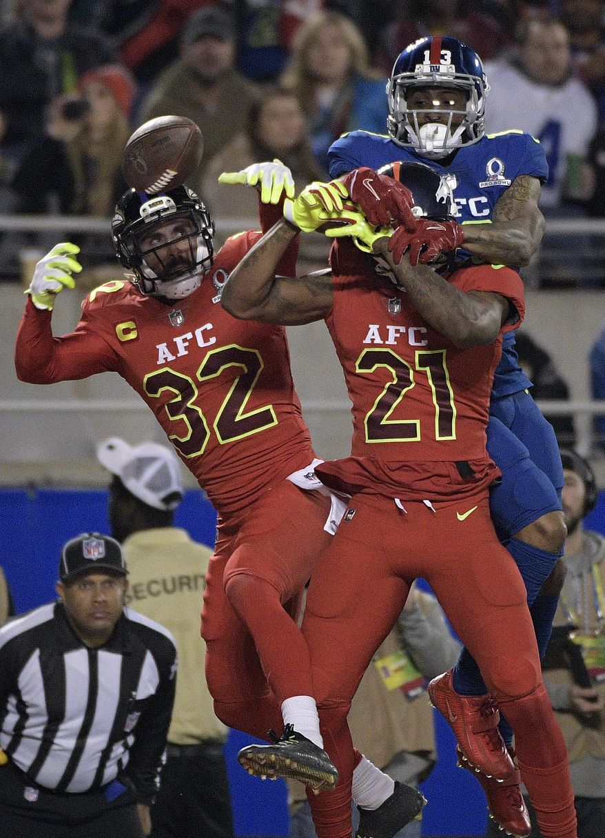 AFC cornerback Aqib Talib (21), of the Denver Broncos and safety Eric Weddle (32), of the Baltimore Ravens, attempt to intercept pass intended for NFC wide receiver Odell Beckham Jr. of the New York Giants, during the second half of the NFL Pro Bowl football game Sunday, Jan. 29, 2017, in Orlando, Fla. (AP Photo/Phelan M Ebenhack)