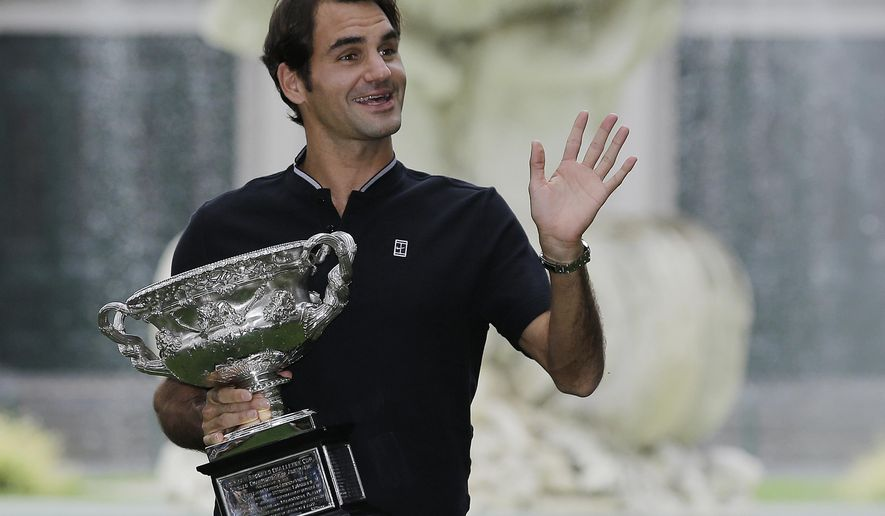 Switzerland's Roger Federer waves to fans as he holds his Australian Open trophy at Carlton Gardens in Melbourne, Australia, Monday, Jan. 30, 2017. Federer defeated Spain's Rafael Nadal in the men's final at the Australian Open tennis championships on Sunday. (AP Photo/Aaron Favila)