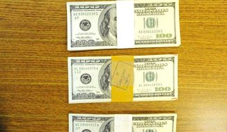 This Wednesday, Jan. 29, 2014 photo shows money that was found by workers going through donated clothing at the Monroe Goodwill store in Monroe, Mich.  While sorting through a recent donation, Tyler  Gedelian came upon a wallet and several envelopes containing what he knew to be a significant sum of money. He contacted the Monroe Police Dept., handing over all the cash, and the wallet bearing an old identification card belonging to the clothes' owner. Police discovered the total amount to be $43,100.00, and were able to track down the relatives who made the donation so that the money can be returned to the family. (AP Photo/The Monroe Evening News, Kim Brent)