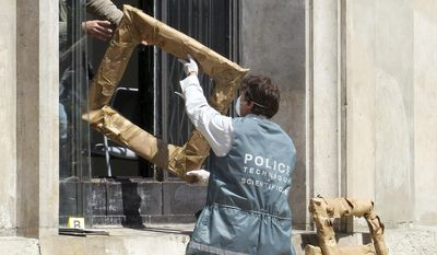 FILE - In this May 20, 2010 file photo,a police officer hands the packed frames of the stolen paintings, to a colleague, from outside the Paris Museum of Modern Art, in Paris. Three people are on trial Monday Jan 30 2017 in Paris accused of involvement in one of the world's biggest art heists, a dramatic 2010 theft of more than $100 million worth of artworks from the Paris Museum of Modern Art _ including a Picasso, a Matisse and other masterpieces. (AP Photo/Jacques Brinon, File)