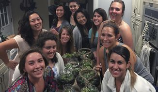 """This May 1, 2015 photo provided by Connie Collins shows a group of friends posing for a photo on Galentine's Day as they celebrated by making terrariums, along with participating in a potluck at the home of Macie Skipwith in San Jose, Calif. Other women have also embraced the made-up holiday that dates to 2010, when Amy Poehler's character on """"Parks and Recreation"""" threw a brunch and called it her favorite holiday of the year. (Connie Colllins via AP)"""