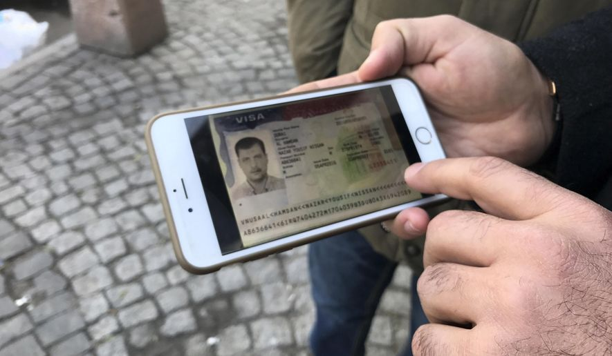 An Iraqi businessman Nazar al-Hamadani shows a phone picture of his Visa to United States during an interview with the Associated Press in Baghdad, Iraq, Monday, Jan. 30, 2017. Iraqis say they are shocked and disappointed with President Donald Trump's order that bans citizens of Muslim-majority countries, including Iraq, from entering United States. (AP Photo/ Ali Abdul Hassan)