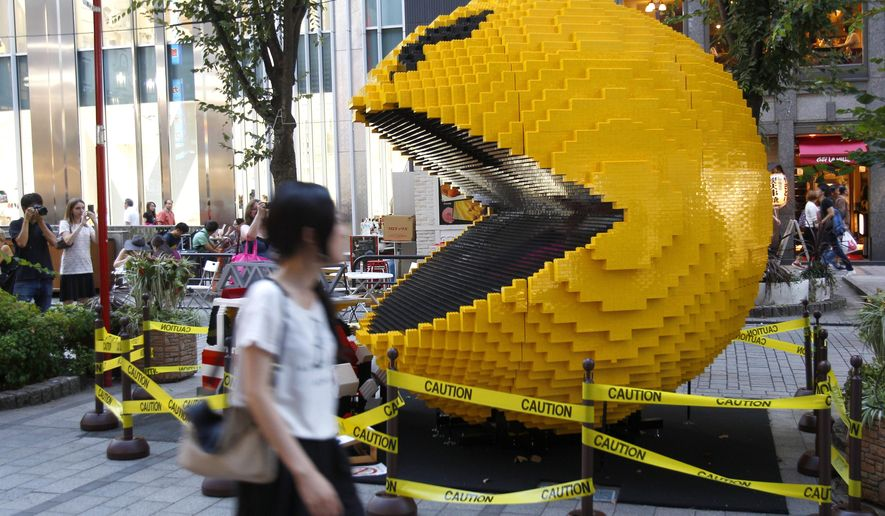 """FILE - In this Aug. 12, 2015, file photo, a woman walks past a three-meter (nine-foot)-tall Pac-Man made of Lego bricks, in Tokyo's Shinjuku area. Masaya Nakamura, the """"Father of Pac-Man"""" who founded the Japanese video game company behind the hit creature-gobbling game, has died on Jan. 22, 2017, at age 91, the company Bandai Namco said. (AP Photo/Ken Aragaki, File)"""