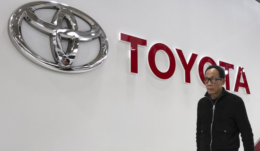 A visitor walks past the log of Toyota Motor Corp. at its showroom in Tokyo, Monday, Jan. 30, 2017. Toyota has relinquished the title of the world's biggest automaker, reporting Monday that it sold 10.175 million vehicles worldwide in 2016, fewer than Volkswagen's 10.31 million. (AP Photo/Shizuo Kambayashi)