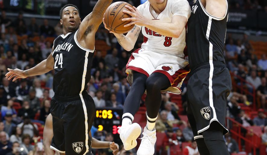 Miami Heat guard Tyler Johnson (8) goes up for a shot against Brooklyn Nets forwards Rondae Hollis-Jefferson (24) and Justin Hamilton during the first half of an NBA basketball game, Monday, Jan. 30, 2017, in Miami. (AP Photo/Wilfredo Lee)