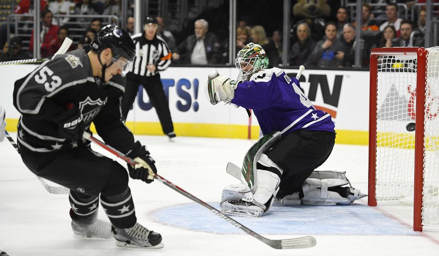 Central Division goalie Devan Dubnyk, right, of the Minnesota Wild, is scored on by Pacific Division forward Johnny Gaudreau, of the Calgary Flames, as forward Bo Horvat, of the Vancouver Canucks, skates by during the first game of an NHL All-Star hockey game at Staples Center, Sunday, Jan. 29, 2017, in Los Angeles. (AP Photo/Mark J. Terrill)