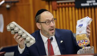 Sen. Simcha Felder, D-Brooklyn asks New York City Mayor Bill de Blasio if he knows the cost of a loaf of bread and a dozen eggs during a joint legislative budget hearing on local government on Monday, Jan. 30, 2017, in Albany, N.Y. (AP Photo/Hans Pennink)