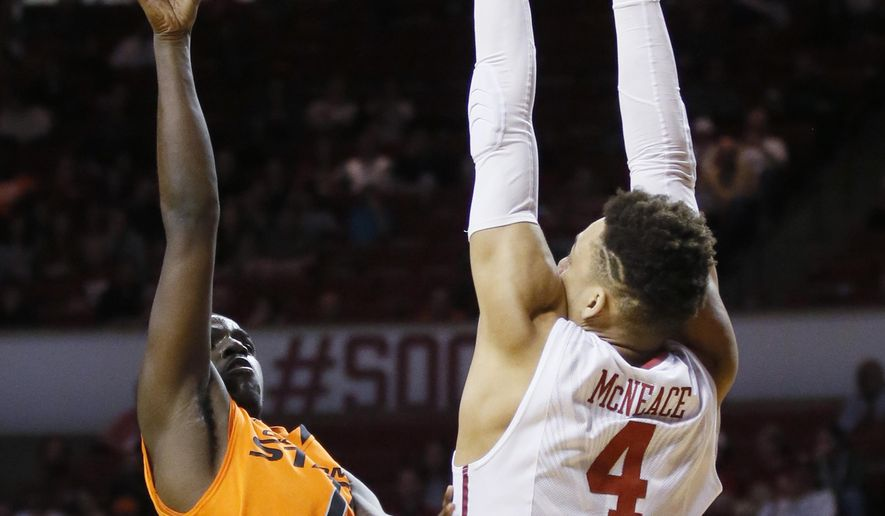 Oklahoma State guard Jawun Evans (1) shoots as Oklahoma center Jamuni McNeace (4) defends in the first half of an NCAA college basketball game in Norman, Okla., Monday, Jan. 30, 2017. (AP Photo/Sue Ogrocki)
